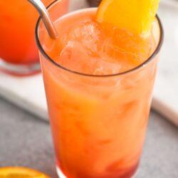 glass of garibaldi cocktail with ice, straw and orange garnish