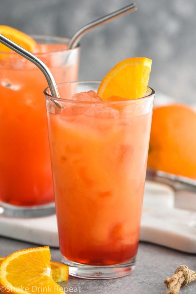 two glasses garibaldi cocktail with ice, straw, and orange garnish
