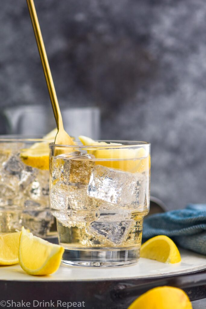 glass of gin and ginger ale with ice and lemon being stirred