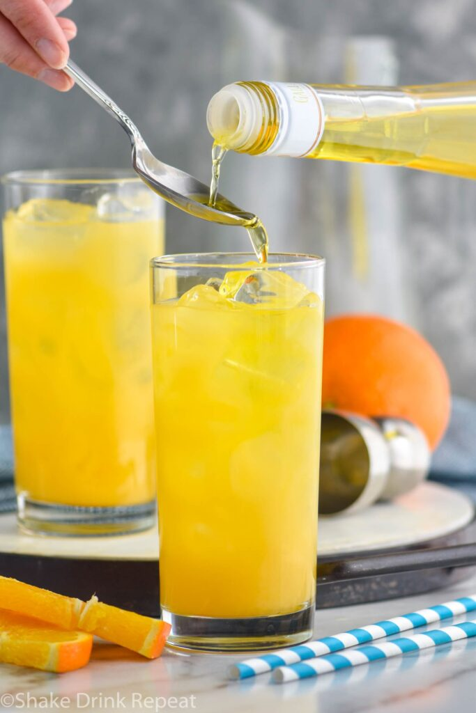 making a Harvey Wallbanger drink recipe with Galliano poured into glass with orange wedge garnish