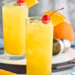 two glasses Harvey Wallbanger drink with orange wedge and cherry garnish