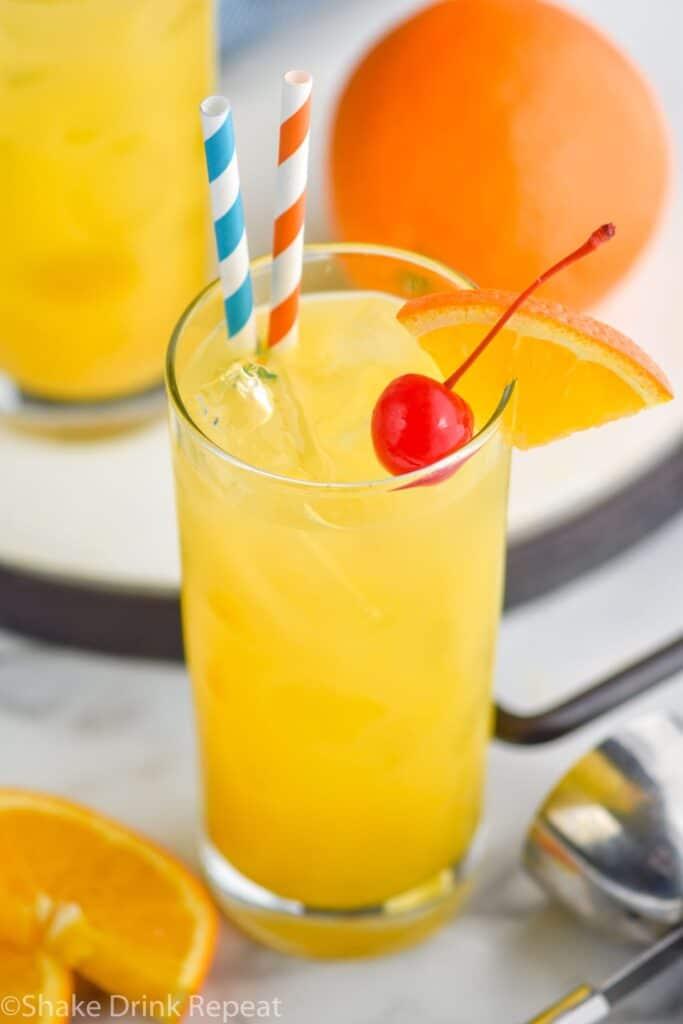 Glass of Harvey Wallbanger drink with straws, orange wedge and cherry garnish