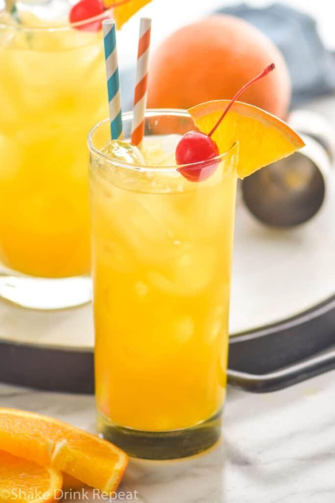 glass of Harvey Wallbanger with straws, orange wedge and cherry garnish