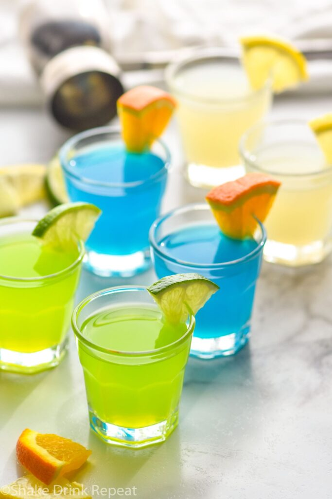 shot glass with green and blue kamikaze shot with orange and lime wedge