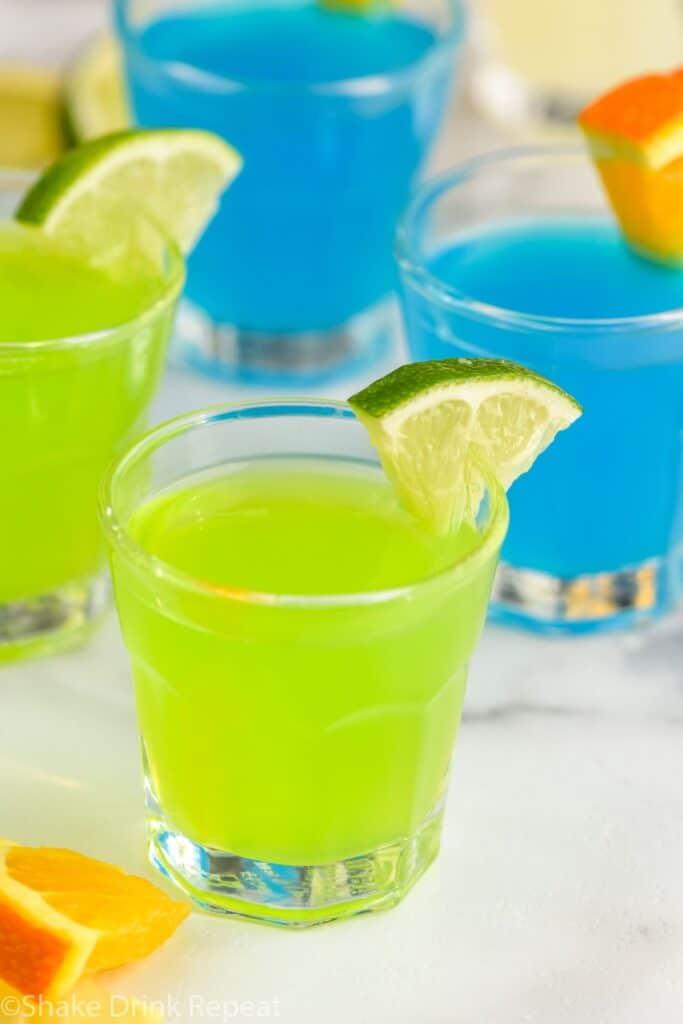 4 kamikaze shots in glasses with lime and orange wedge garnish