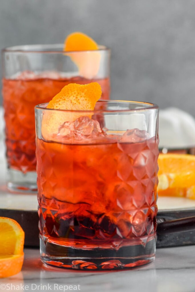 two glasses of Negroni with ice and orange twist
