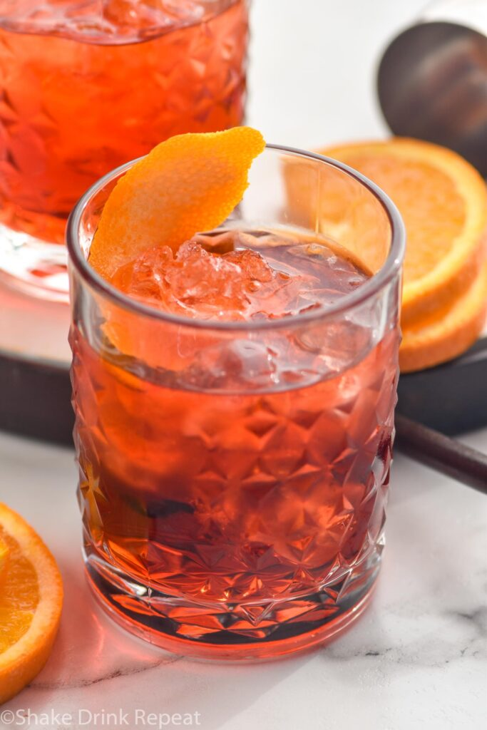 glass of Negroni drink with ice and orange twist