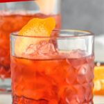 glass of Negroni cocktail with ice and orange twist