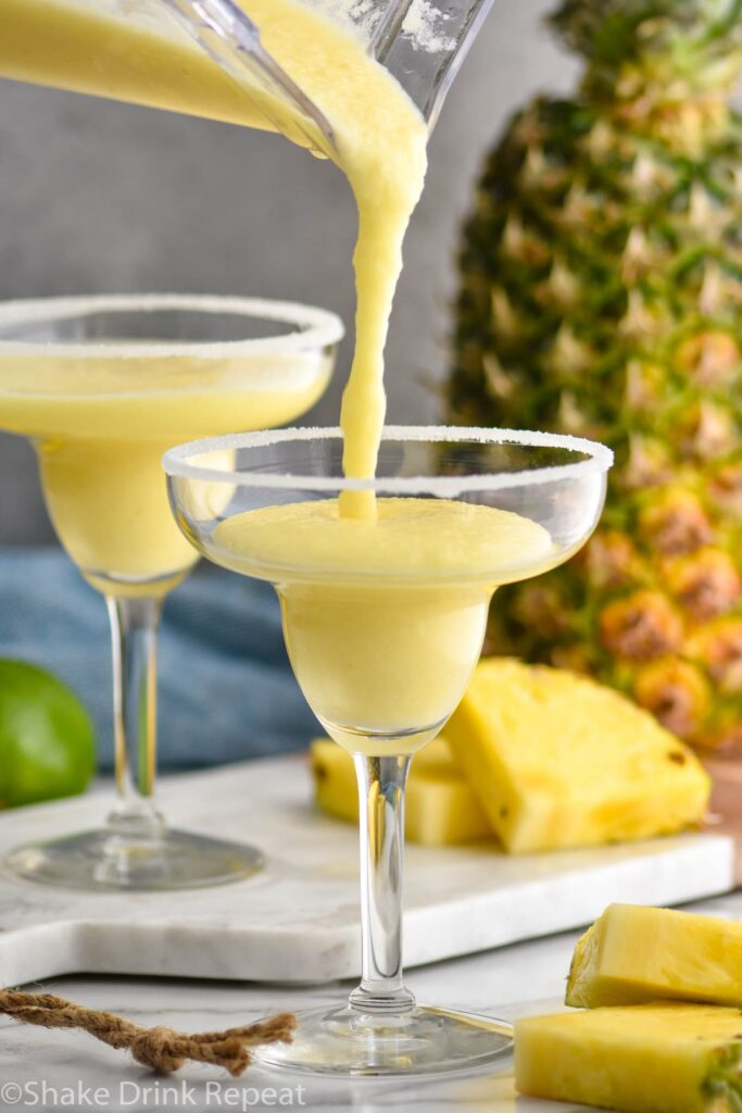 two glasses pineapple margarita recipe being poured with salted rim