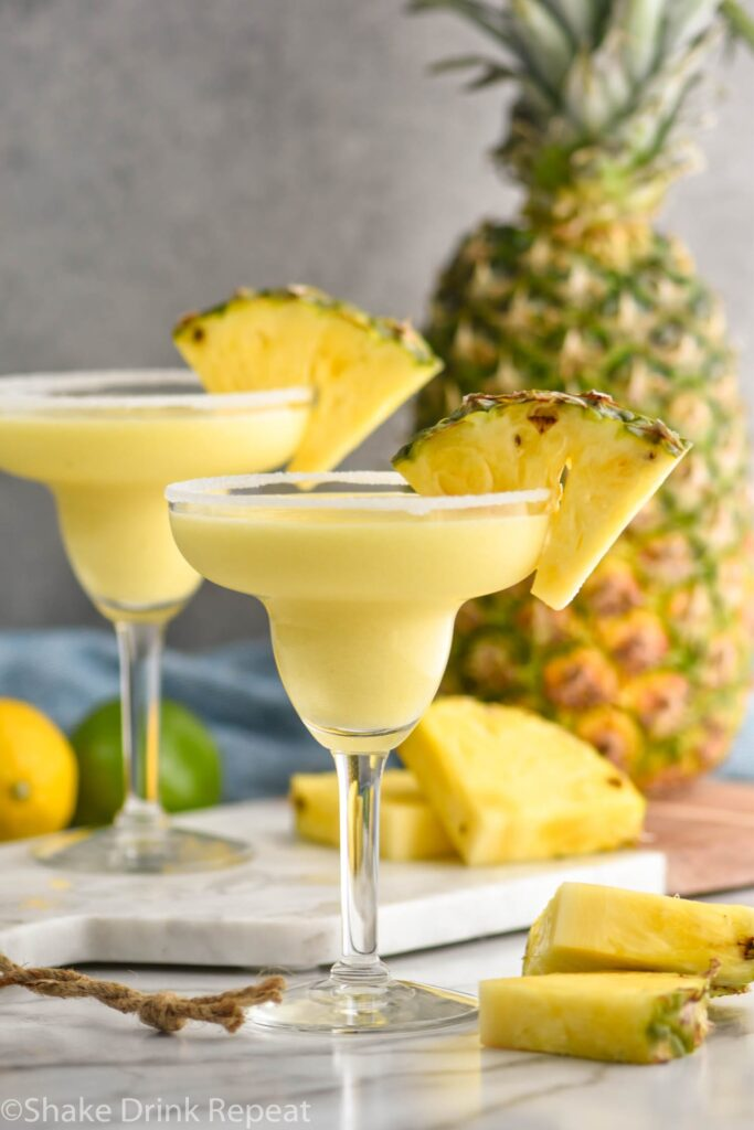 two glasses of pineapple margarita with salted rim surrounded by lemons and limes