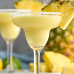 two glasses of pineapple margarita with salted rim
