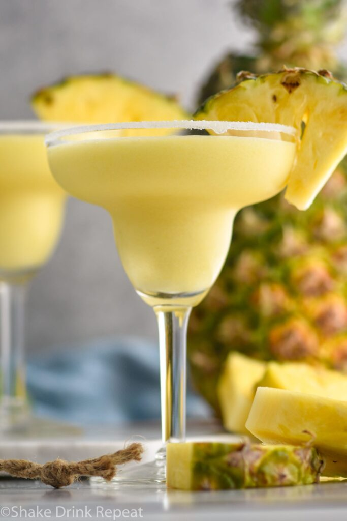 glass of pineapple margarita with salted rim