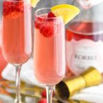 two glasses pink mimosa recipe with ingredients, rosé, raspberries and lemon