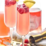 two glasses pink mimosa recipe with raspberries and ingredients