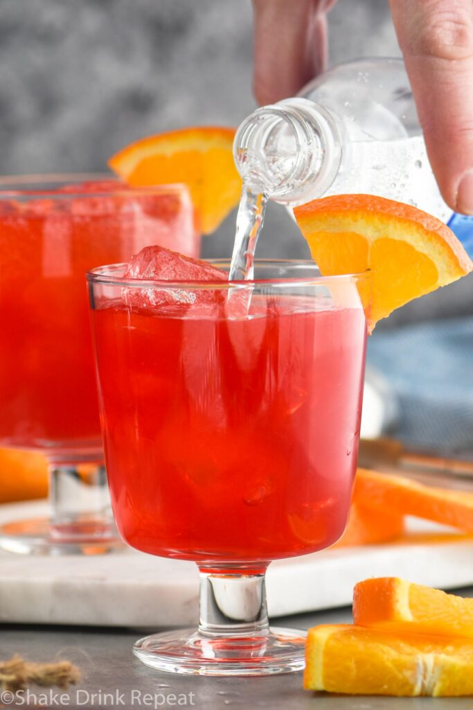 two glasses of sloe gin fizz recipe ingredients with orange slice garnish and club soda poured