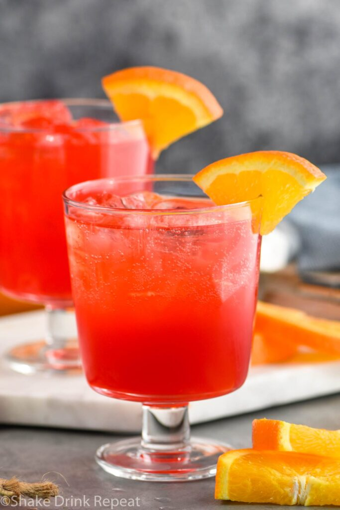two glasses of sloe gin fizz with ice and orange slice garnish