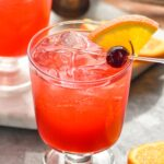 two glasses of slow gin fizz with orange slice and cherry garnish and jigger