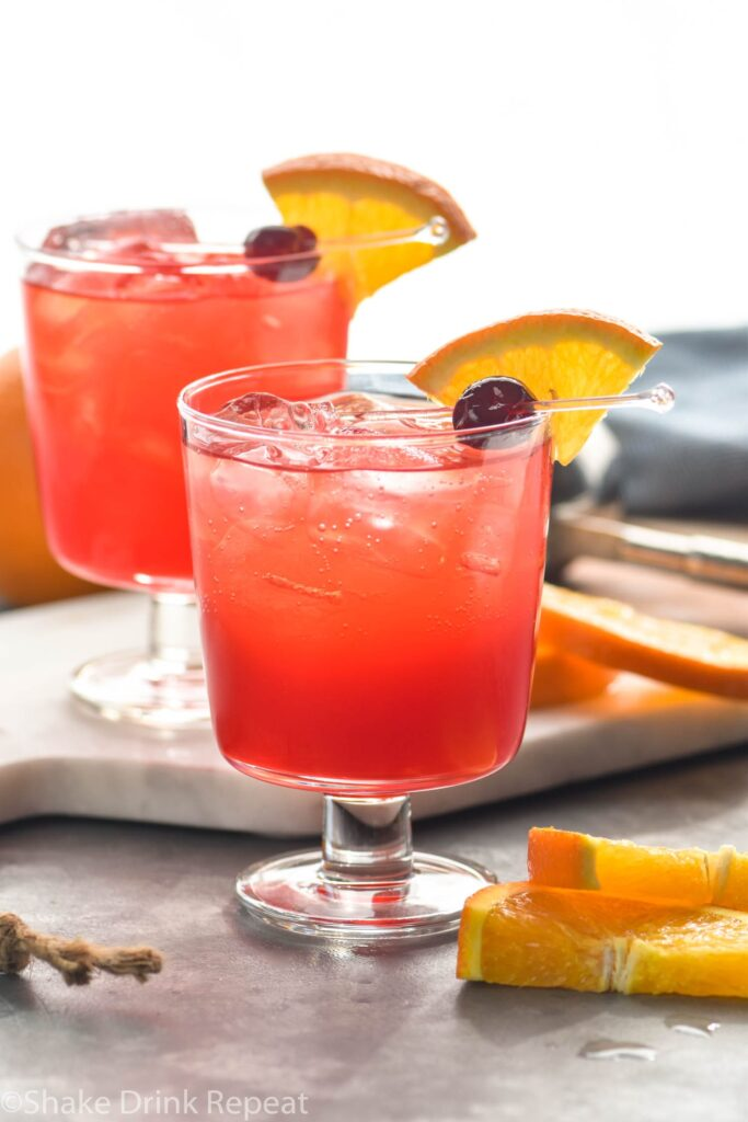 two glasses of sloe gin fizz cocktail with orange slice and cherry garnish