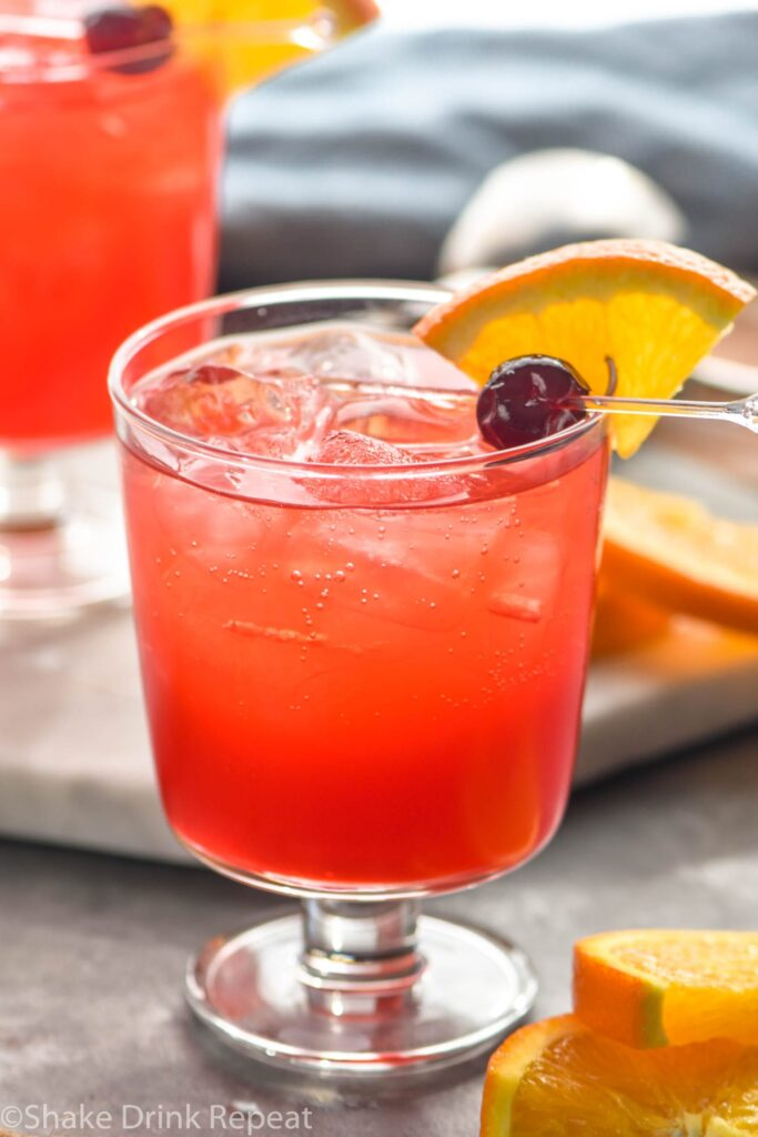Glass of Sloe gin fizz with ice and cherry and orange wedge garnish