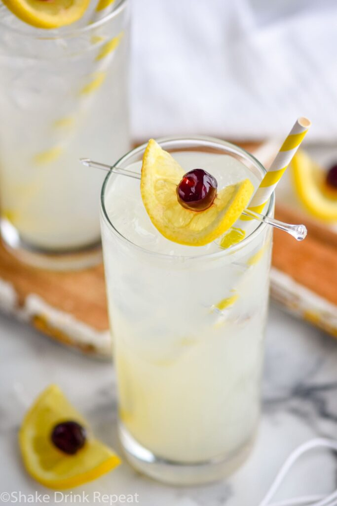 two glasses of tom collins with ice, lemon, cherry