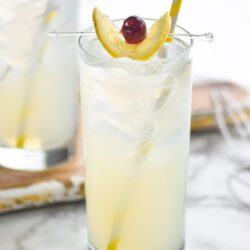 two glasses tom collins cocktail with ice, lemon, and cherry