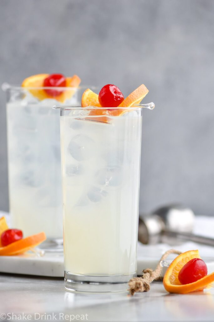 two glasses of vodka collins with ice, orange slice and cherry garnish