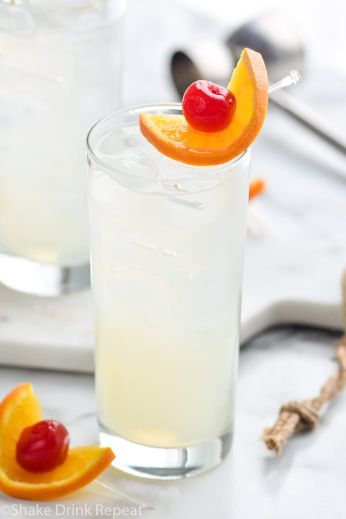glass of vodka collins with ice, orange slice and cherry