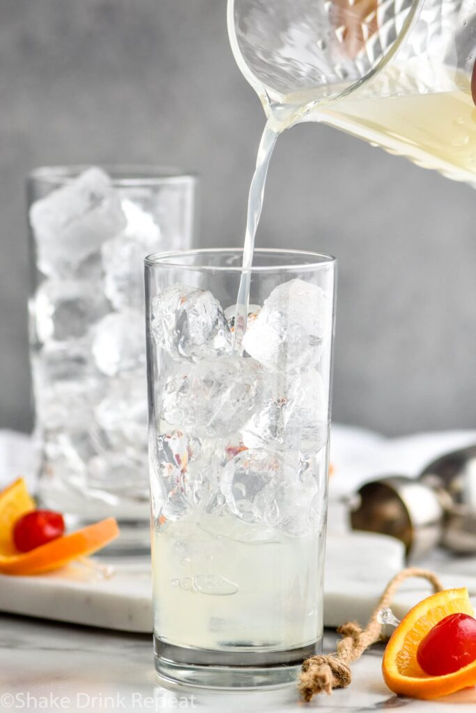 glass of vodka collins ingredients with ice, orange slice and cherry garnish