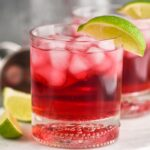 Glass of Vodka Cranberry with ice and lime wedge and recipe ingredients in background