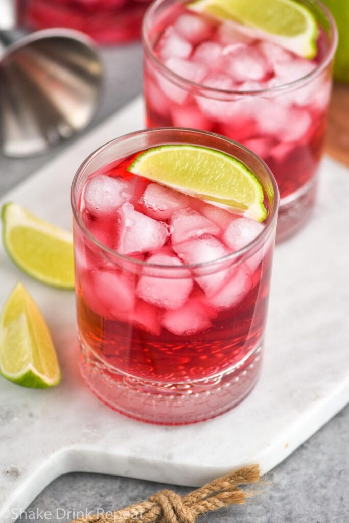 two glasses of vodka cranberry recipe with ice, lime wedges and jigger in background