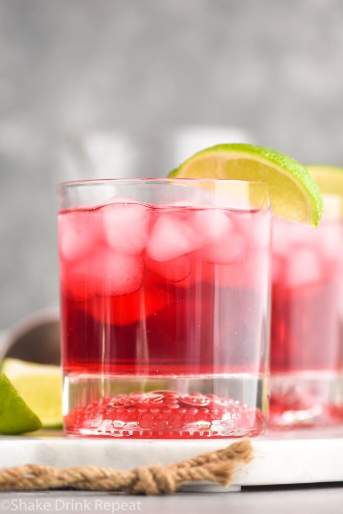 Glass of Vodka Cranberry recipe with ice and lime wedge
