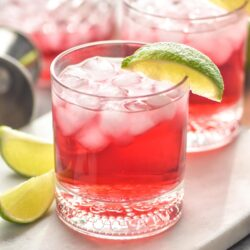 Two glasses of Vodka Cranberry recipe with ice and lime wedges