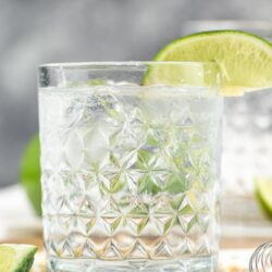 glass of vodka tonic cocktail with ice and lime wedge
