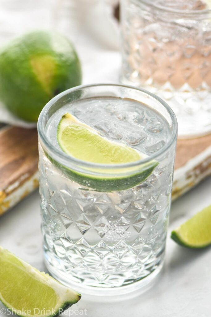 glass of vodka tonic with ice and lime wedge