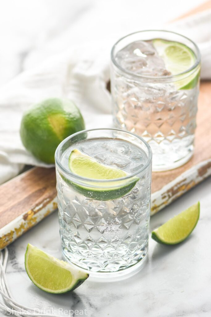 two glasses vodka tonic with ice and lime wedge