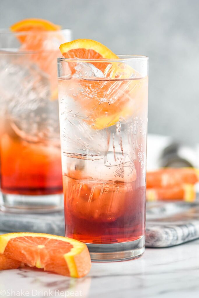 two glasses of americano cocktail with ice and orange slice garnish