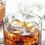 Glass of Black Russian with ice, surrounded by coffee beans