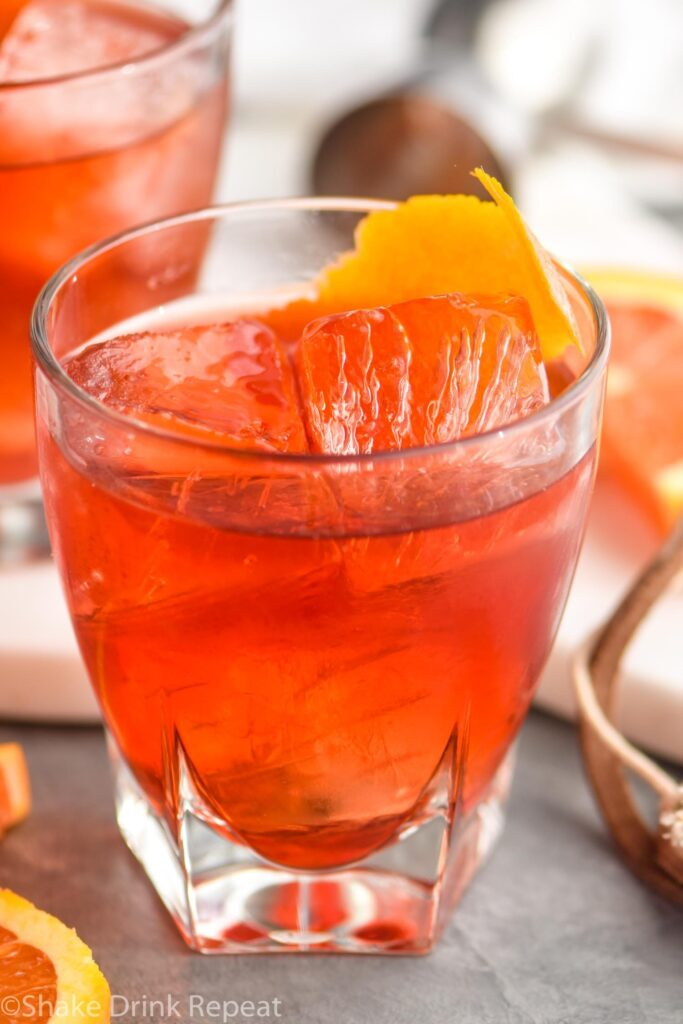 glass of boulevardier cocktail with ice and orange garnish
