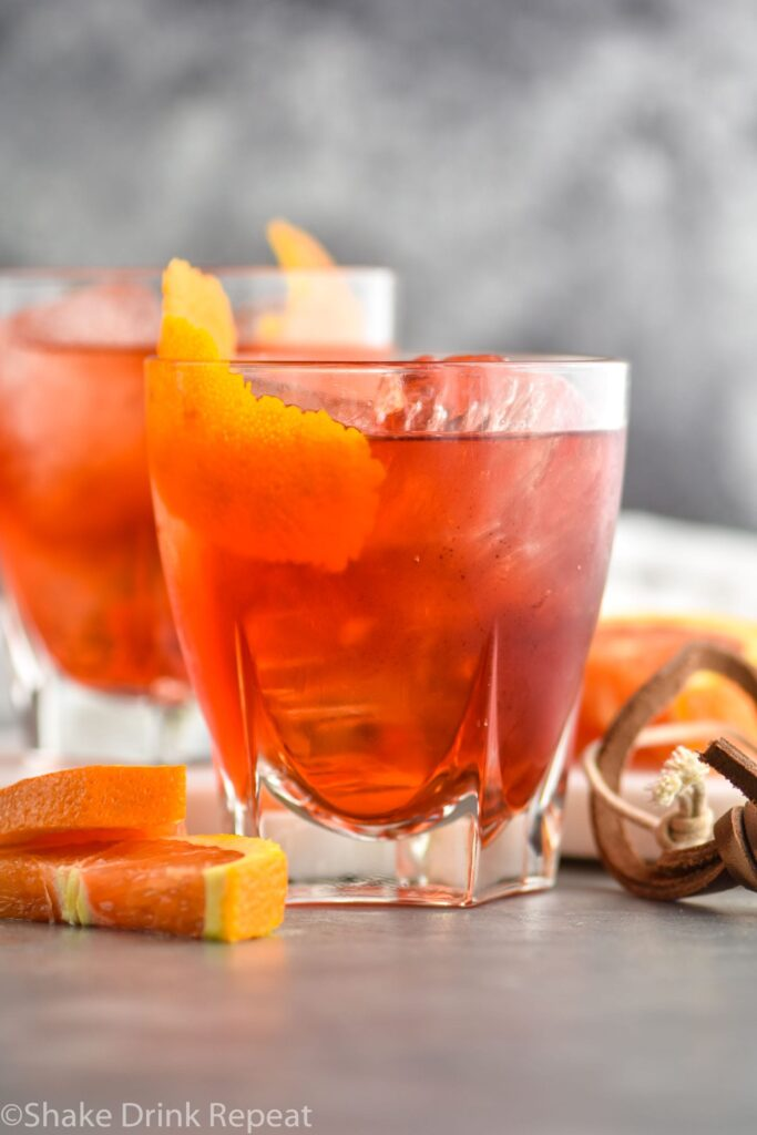 two glasses of boulevardier with ice and orange garnish