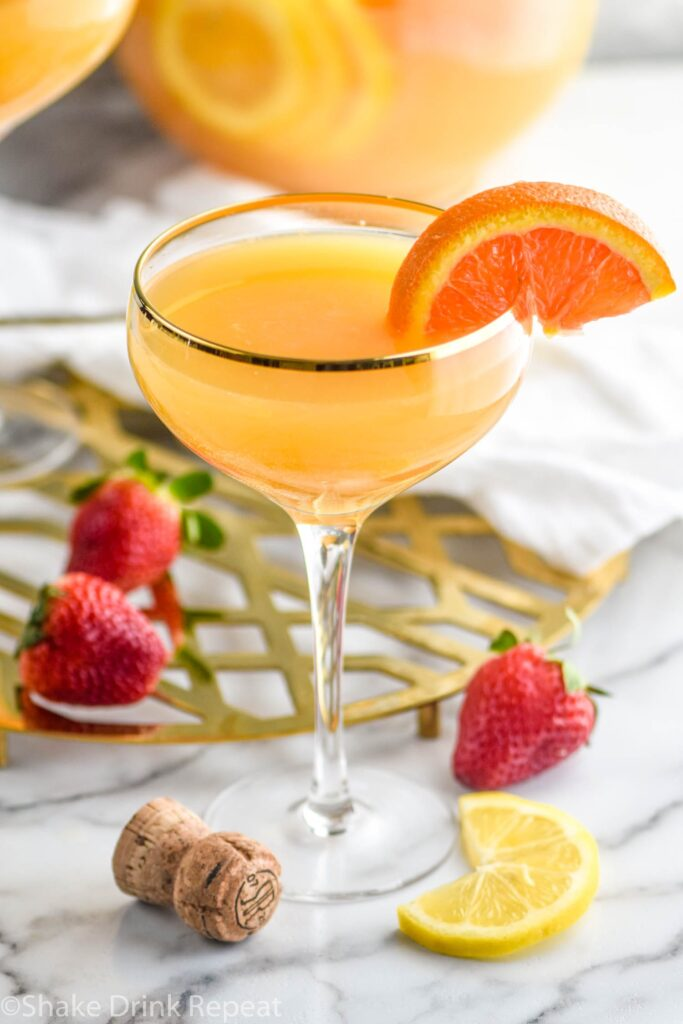 glass of mimosa sangria with orange slice and strawberries