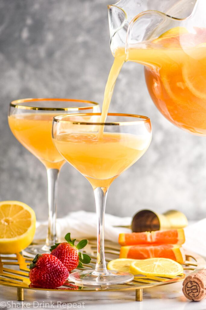 two glasses mimosa sangria recipe ingredients with orange slices and strawberries