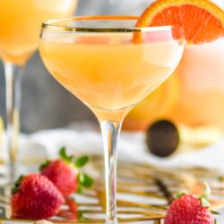 Two glasses mimosa sangria recipe with orange wedges and strawberries