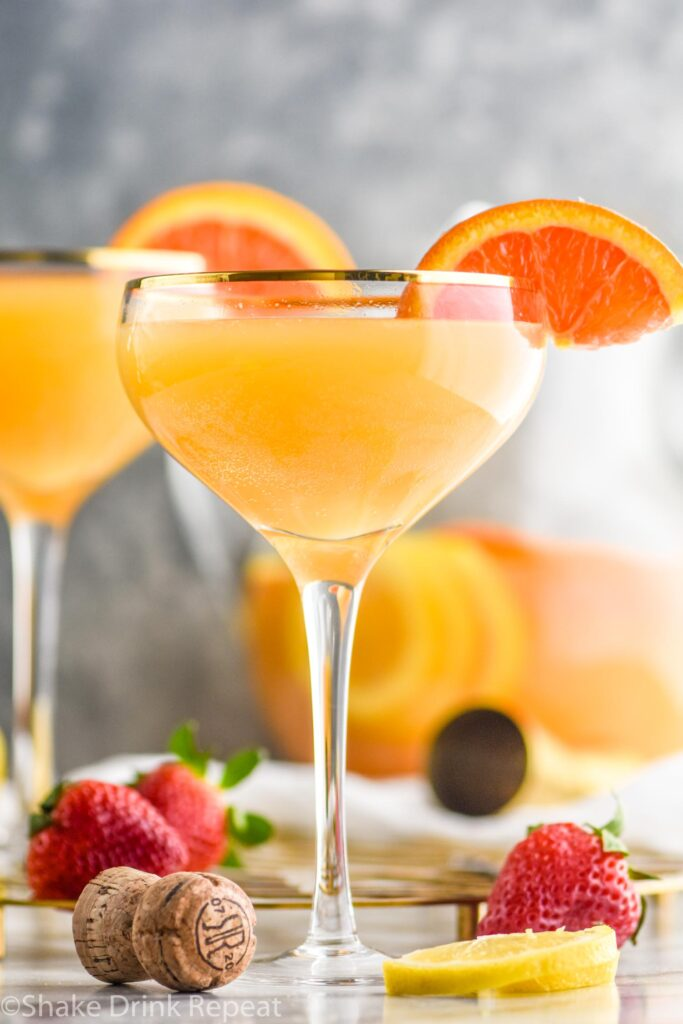 two glasses mimosa sangria with orange slices and strawberries