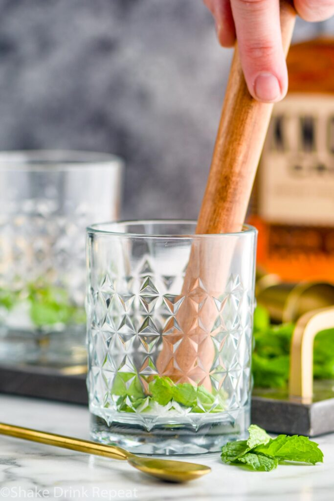 making mint julep recipe with ingredients fresh mint and bourbon