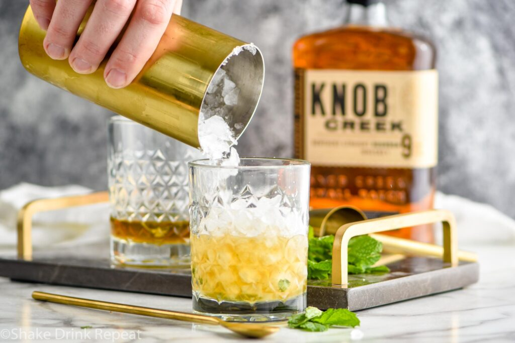 Making mint julep cocktail with shaved ice, bourbon and mint leaves