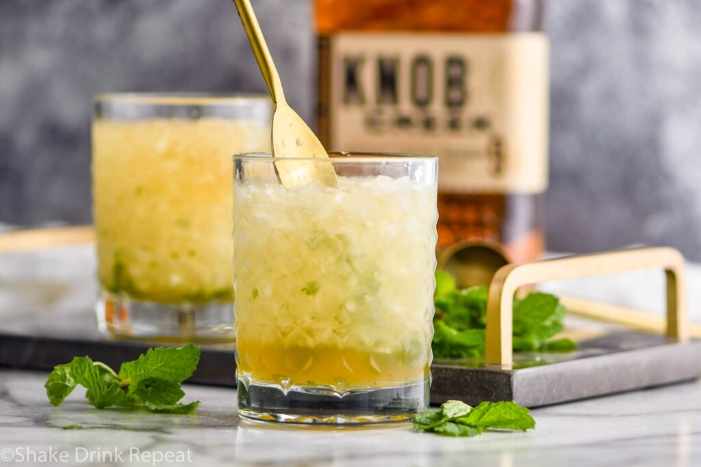 two glasses of mint julep cocktail with bourbon and ice