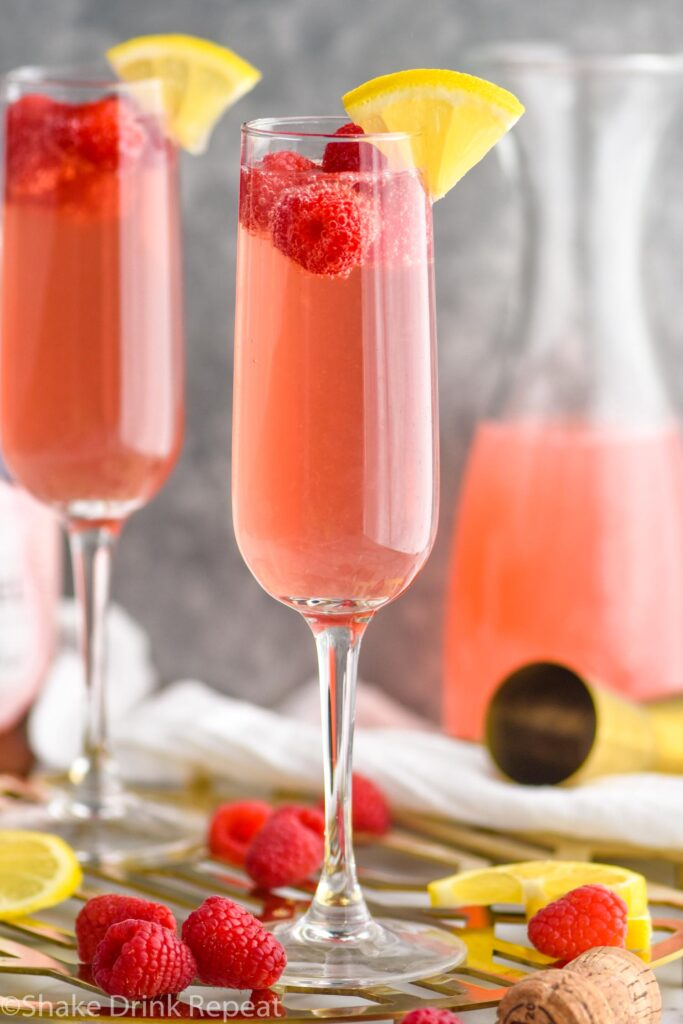 two glasses pink mimosa recipe with lemonade and raspberries