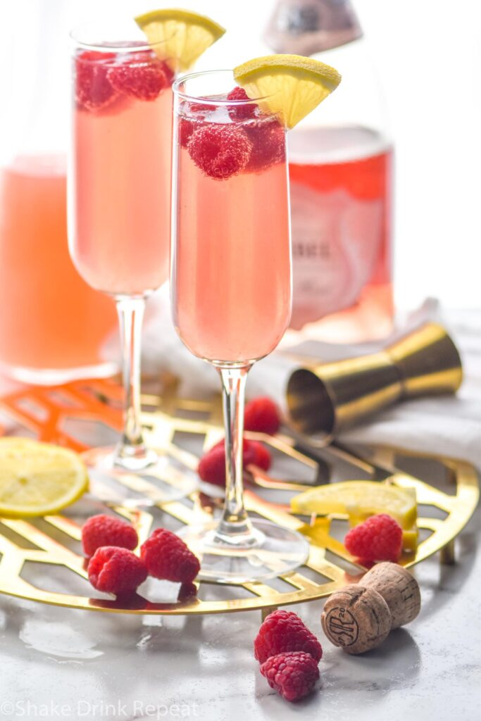 two glasses of pink mimosa with rosé, sliced lemon and raspberries