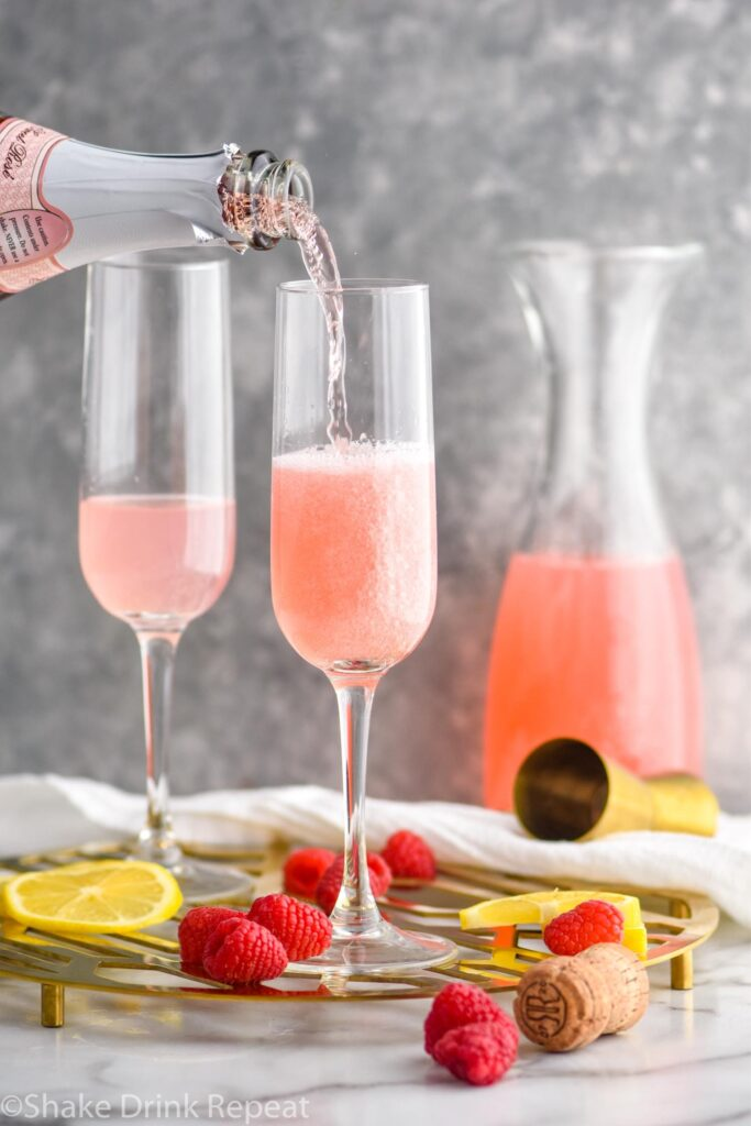 champagne flutes with pink mimosa ingredients and rose