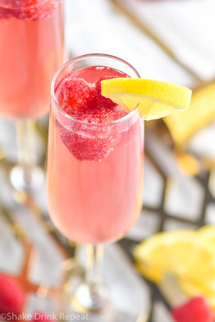 glass of pink mimosa with lemon slice and raspberries